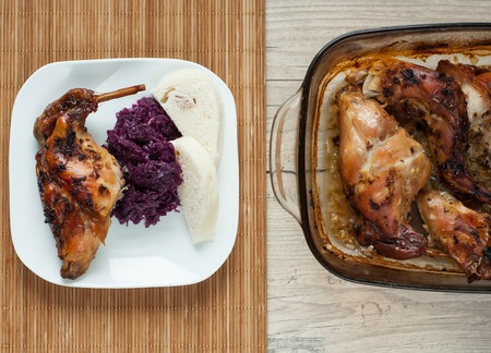 rabbit meat roaster with onion cumin and garlic on wooden vintage table with cabbage and dumpling photo