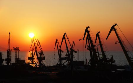 Silhouettes of port cranes on a background of a rising sun.