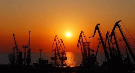 Silhouettes of port cranes on a background of a rising sun. photo