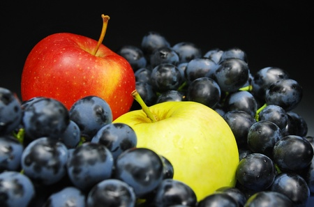 Close-ups of fresh grape and apples on black background