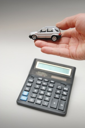 Calculator and hand with toy car photo