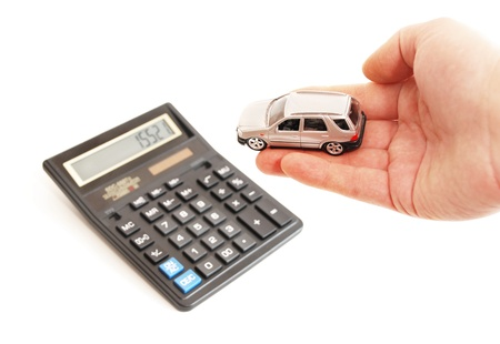 Calculator and hand with toy car on white background. Stock Photo - 9119336