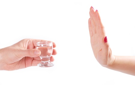 reject: Female hand reject a glass of alcohol. Isolated on white.
