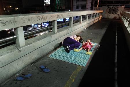 vagabundos: Mujer sin hogar y un niño que duerme en la calle de Bangkok, Tailandia Editorial