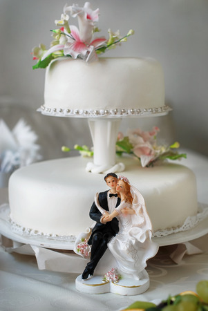 Wedding cake with bride and groom figurines, decorated with  lilies.