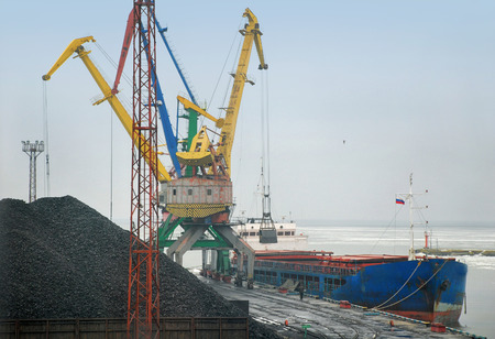 overhead crane: Crane loading coal to ship in port