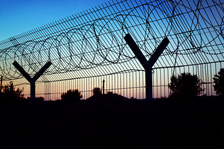 wire fence: Restricted area - fence with barbed wire. Stock Photo