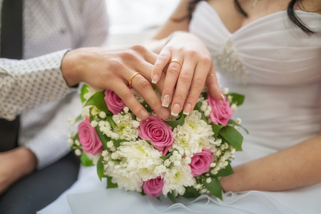 Golden wedding rings on bride and groom fingers with flowers Stock Photo