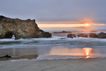 ocean state: Sandy coves and rocky cliffs of the Pacific Ocean. Sunset at Pescadero State Beach, California