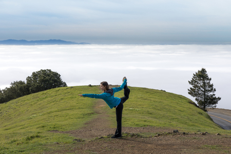 Yoga in Nature. Warrior yoga posture of young woman above the clouds. Mount Tamalpais, California, USA.