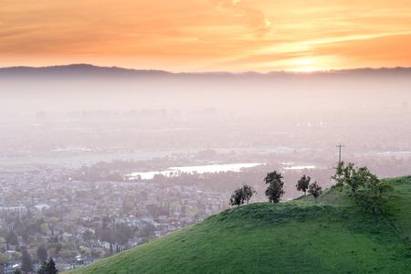 숨이 멎을듯한 실리콘 밸리 선셋. 해밀턴 마운트에서 녹색 언덕과 일몰 하늘와 안개에 산타 클라라 밸리. 스톡 콘텐츠