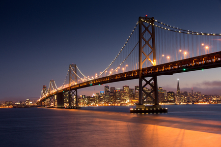 Dusk over San Francisco-Oakland Bay Bridge and San Francisco Skyline, California, USA. Фото со стока