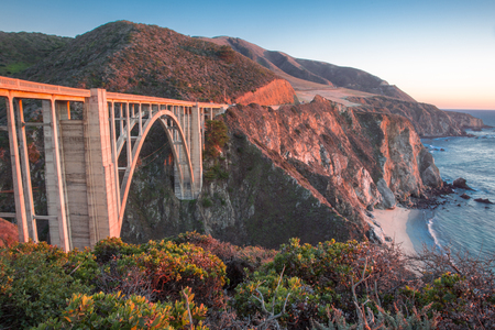 Sunset over Bixby Bridge, Big Sur, California, USA. Bixby Creek Bridge, also known as Bixby Bridge, is a reinforced concrete open-spandrel arch bridge in Big Sur, California. The bridge is located 120 miles south of San Francisco and 13 miles south of Car