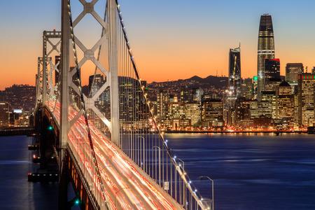 San Francisco Bay Bridge i Skyline o zmierzchu. Jasny wieczór nad nabrzeżem San Francisco z świątecznymi światłami z wyspy Yerba Buena w Kalifornii, USA.