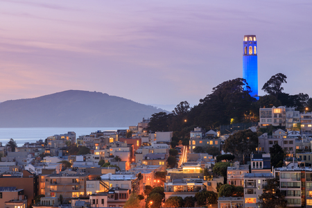 Coit Tower on Telegraph Hill with San Francisco Bay and Angel Island in the background at dusk. Taken from a downtown building rooftop. San Francisco, California, USA. Stock fotó