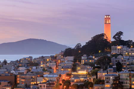 Coit Tower on Telegraph Hill with San Francisco Bay and Angel Island in the background at dusk. Taken from a downtown building rooftop. San Francisco, California, USA.