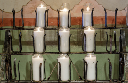 Burning votive candles in a church. Mission Soledad, California, USA. Stock Photo