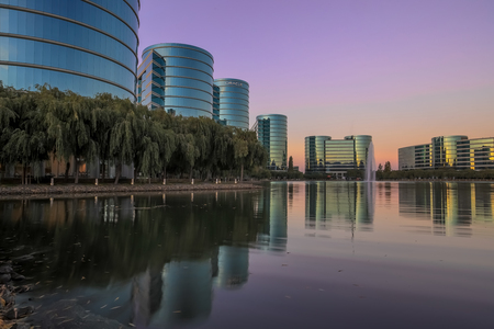 Redwood Shores, California - September 22, 2018: Oracle headquarters and lake with sunset skies. Oracle Corporation is an American multinational computer technology corporation headquartered in Redwood Shores, California.