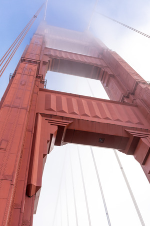 Golden Gate Bridge tower in the fog, looking up from the base. San Francisco, California, USA. Stock Photo