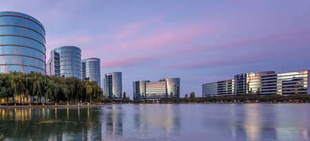 Redwood Shores, California - September 27, 2018: Oracle headquarters and lake with twilight sky panoramic view. Oracle Corporation is an American multinational computer technology corporation headquartered in Redwood Shores, California.