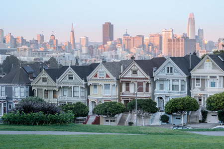 Sunset Over The Painted Ladies of San Francisco. Iconic Victorian Houses and San Francisco Skyline in Alamo Square, San Francisco, California, USA.