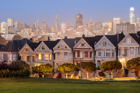 Dusk over the Painted Ladies of San Francisco. Iconic Victorian Houses and San Francisco Skyline in Alamo Square, San Francisco, California, USA.