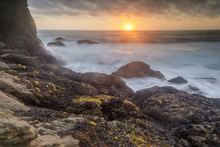 Rugged coastline sunset over Gray Whale Cove State Beach. Half Moon Bay, San Mateo County, California, USA. Imagens