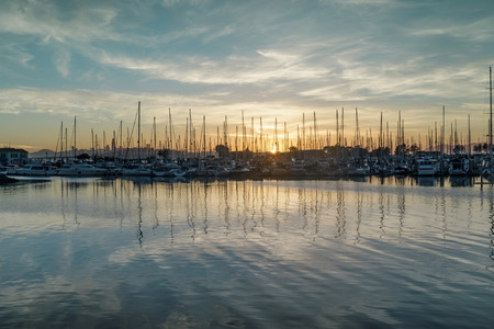 Colors of Emeryville Marina. Sailboats moored in San Francisco Bay with sunset skies and water reflections. Alameda County, California, USA. Stock Photo