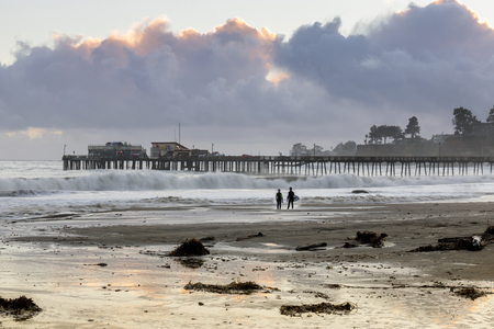 Capitolastrand en werf in stormachtige wolkenzonsondergang en surferssilhouet. Capitola, Santa Cruz County, Californië, VS.