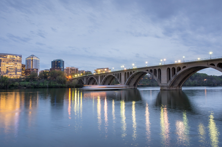 Dusk over Key Bridge and Rosslyn from Georgetown in Washington DC, USA. The Key Bridge spans the Potomac River, connecting the Georgetown neighborhood in the District of Columbia with the neighborhood of Rosslyn in Arlington County, Virginia. Stock Photo