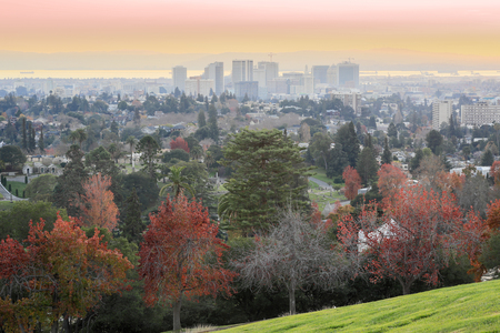 Sunset views of Oakland Downtown and San Francisco Bay from a hilltop in Mountain View Cemetery. Oakland, Alameda County, California, USA. Stock Photo