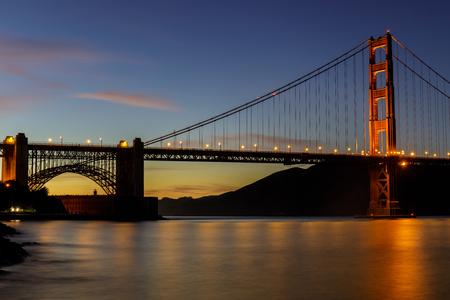 Twilight lights over the Golden Gate Bridge as seen near Fort Point. San Francisco, California, USA.