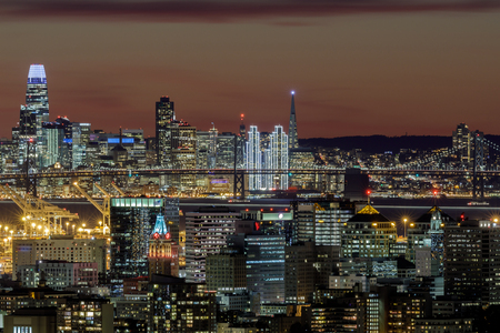 Oakland and San Francisco Twilight Skylines Illuminated with Holiday Lights. Shot on 2019 New Years Eve from Oakland Hills, California, USA.
