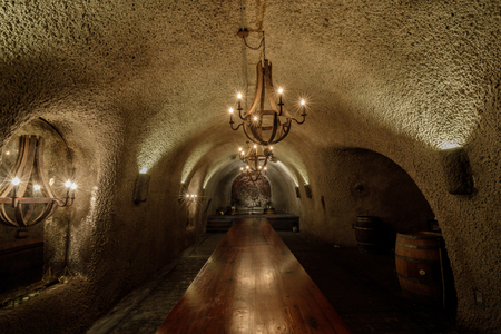 Kenwood, California - April 28, 2019: VIP Dining Room in Cave of Kundy Winery in Sonoma Valley. The VIP Dining Room is located at the end of the wine aging caves with its stage of iron red volcanic ro