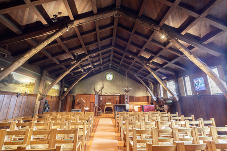 San Francisco, California - May 11, 2019: Interiors of Swedenborian Church in Pacific Heights. With its exposed wooden beams, nature-themed decor, and a fireplace crackling with smoky flames, this chu