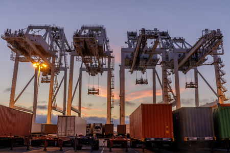 Shipping Container Cranes and Trucks with Sunset Sky in the Port of Oakland. Oakland International Container Terminal, Alameda County, California, USA.
