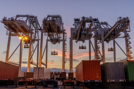 Transportowe dźwigi kontenerowe i ciężarówki z Sunset Sky w porcie Oakland. Międzynarodowy terminal kontenerowy w Oakland, Hrabstwo Alameda, Kalifornia, USA.