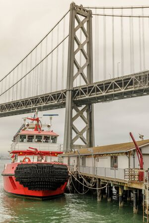 San Francisco Fireboat moored with the Bay Bridge in the background. The new fireboat's main job is to keep the city's water system flowing in case of a disruption. The boat can pump 18,000 gpm into the system at various locations. 写真素材