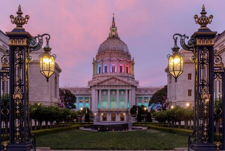 Twilight skies over San Francisco City Hall illuminated in rainbow colors for the Pride Parade. San Francisco, California, USA.