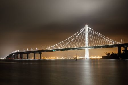 Reflections of fog and water on the Bay Bridge eastern span on a summer night. Yerba Buena Island, San Francisco, California, USA.