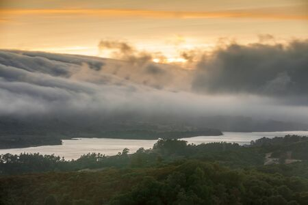 Fog Rolling over Crystal Springs Reservoir as seen from a vista point off Highway 280 on a Summer Sunset. Redwood City, San Mateo County, California, USA.
