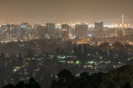 Oakland and San Francisco Cityscapes on a Hazy Summer Night. Oakland Hills, Alameda County, California, USA.