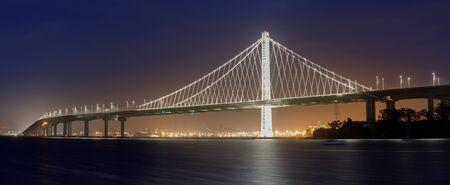 Eastern span of San-Francisco-Oakland Bay Bridge panoramic view at Night. Shot from Treasure Island, San Francisco, California, USA.