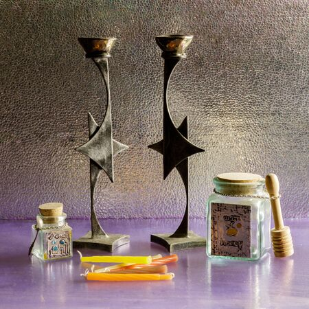 Jewish Still Life: Candlestick Holders in Star of David's shape, Candles, Sugar and Honey Jars, on glass and metal reflector background.