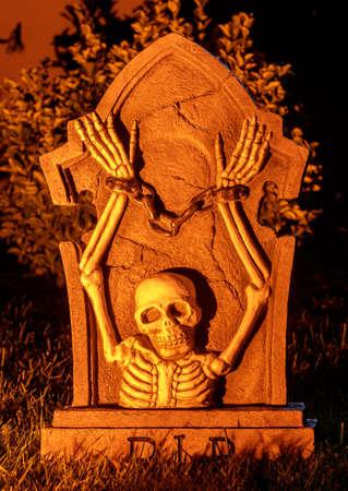 Handcuffed Skeleton Emerging from Gravestone Фото со стока