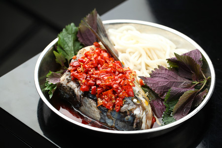 fish head: Fish head and vegetables served on a plate Stock Photo