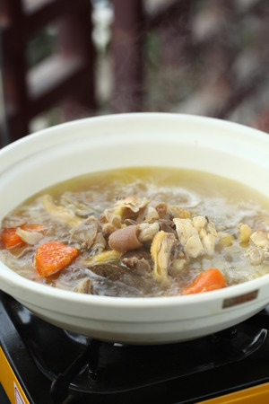 broth: Chinese broth in a clay pot on a stove Stock Photo
