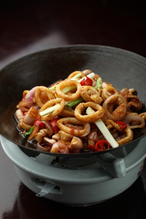 stir fried: Stir fried chili squid in a wok on a stove Stock Photo