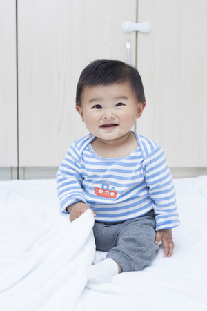 white blanket: Cute Chinese baby boy sitting on a white blanket