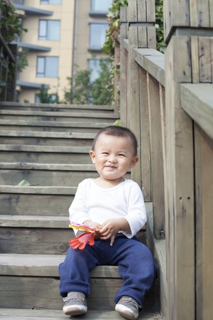 bebes lindos: Happy Chinese baby boy playing a toy on stairs, shot in Beijing, China Foto de archivo